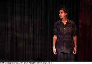 Primary view of object titled '[Performer Wearing Graduation Cap on Stage]'.