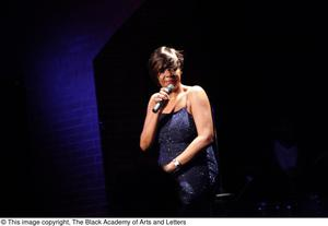 Primary view of object titled '[Singer in sparkly dress in spotlight]'.