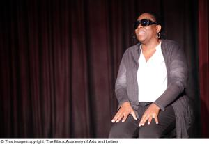 Primary view of [Performer sitting on stage wearing sunglasses]