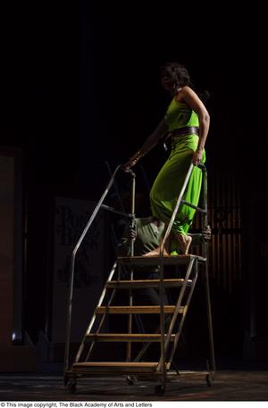 Primary view of object titled '[Performer in green dress on stairs]'.