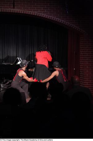 Primary view of object titled '[Performers in red and black on stage]'.