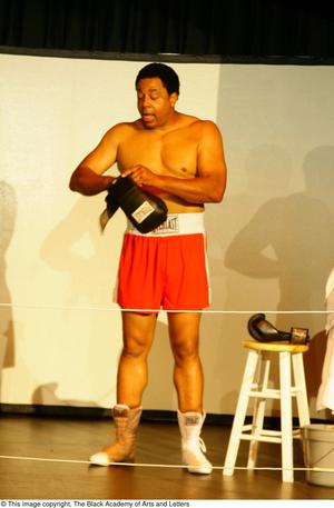 Primary view of object titled '[Vincent Cook Putting on Boxing Gloves on Stage]'.