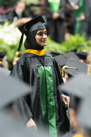 Primary view of object titled '[Graduate Student Walking with her Diploma]'.