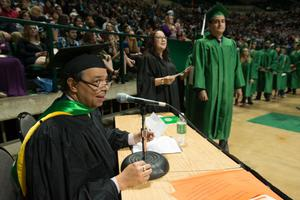 Primary view of object titled '[Faculty Member Annoucing Names at Bachelor Commencement Ceremony]'.