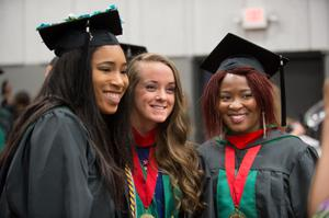 Primary view of object titled '[Three graduate students at commencement ceremony]'.