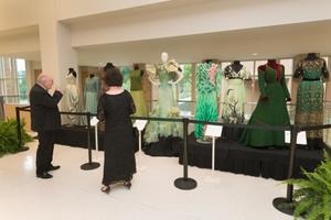 Primary view of object titled '[Guests looking at fashion dresses displayed during the Wingspan Gala]'.