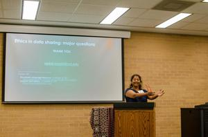 [Shobhana Chelliah gesturing behind a podium at the 2017 Symposium on Developing Infrastructure for Computational Resources on South Asian Languages]