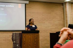 [Shobhana Chelliah standing behind a podium at the 2017 Symposium on Developing Infrastructure for Computational Resources on South Asian Languages]