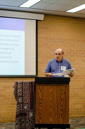 [Gary Simons standing behind a podium at the 2017 Symposium on Developing Infrastructure for Computational Resources on South Asian Languages]