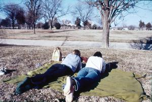 Primary view of object titled '[Two people laying on a picnic blanket]'.