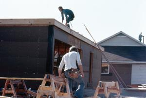 Primary view of object titled '[Two men doing construction on a home]'.