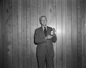Primary view of [Man holding up a Bright Shine bottle]