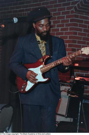 Primary view of object titled '[Medium long shot of guitarist Ras Kumba]'.