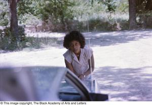 Primary view of object titled '[Photograph of a woman leaning towards the trunk of a vehicle]'.