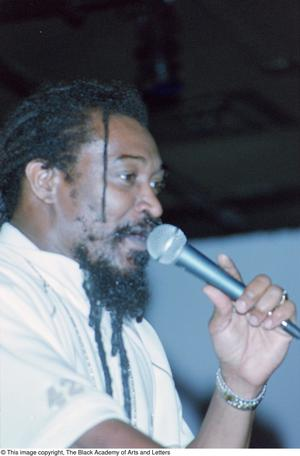 Primary view of object titled '[Close-up of Ras Tumba's profile while singing into microphone]'.