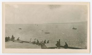 Primary view of [Photograph of a crowd of people sitting on a dock]