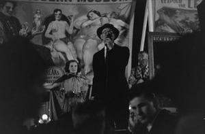 Primary view of [Photograph of a man speaking on stage at a circus]