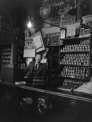 Primary view of [Photograph of a cashier behind a counter]