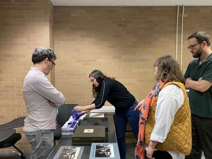 Primary view of [UNT faculty and Keliy Anderson-Staley viewing photography books]