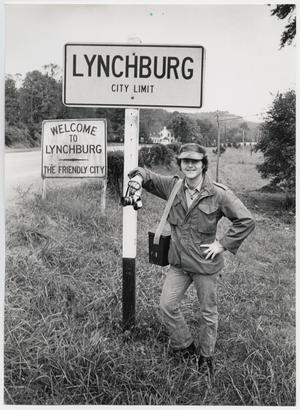 Primary view of object titled '[Junebug Clark leans on a sign for the city of Lynchburg, TN]'.