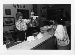 Primary view of object titled '[Female staff member and student at reception desk in Maple Hall, North Texas State University]'.