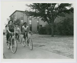 Primary view of object titled '[Female students on bicycles in front of West Hall at North Texas State University]'.