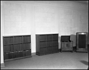 Primary view of object titled '[Record Player and Two Bookcases Inside an Unidentified Building]'.