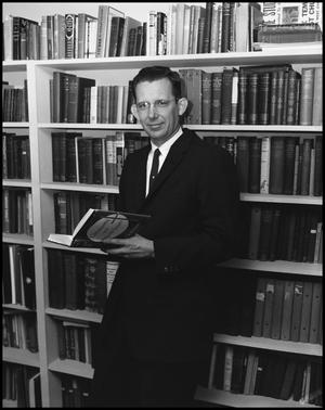 Primary view of object titled '[Dr. Coble Posing with Books in Suit]'.