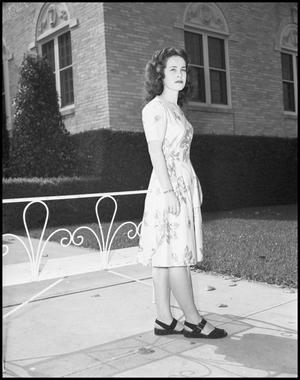 Primary view of object titled '[Woman stands near bench]'.