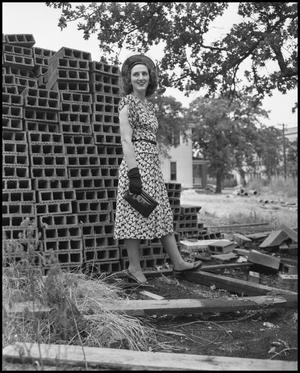 Primary view of object titled '[Woman stands next to a pile of bricks]'.