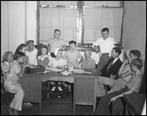 Primary view of object titled '[Students gathered around a desk]'.