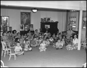 Primary view of object titled '[Children and teachers gather on the floor]'.