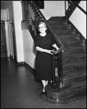 Primary view of object titled '[Woman stands at the bottom of the stairs]'.