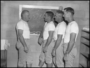Primary view of object titled '[Coach talking to three football players]'.
