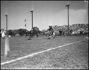 Primary view of object titled '[A Play During a Football Game of Player Running, 1942]'.