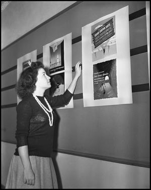 Primary view of object titled '[Young woman looks at a poster on the wall]'.