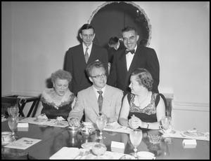 Primary view of object titled '[Five people sitting at a formal dining table]'.