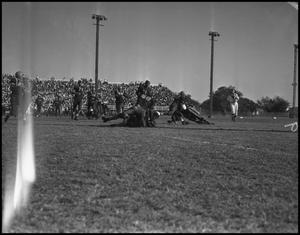 Primary view of object titled '[Football Players Tackling Each Other During a Play, 1942]'.