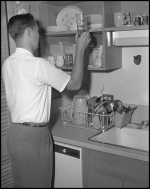 Primary view of object titled '[Man in Kitchen with Cup]'.