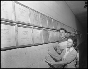 Primary view of object titled '[Two students looking at wall of awards]'.