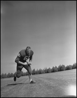 Primary view of object titled '[Football Player No. 61 Running Low on the Field]'.