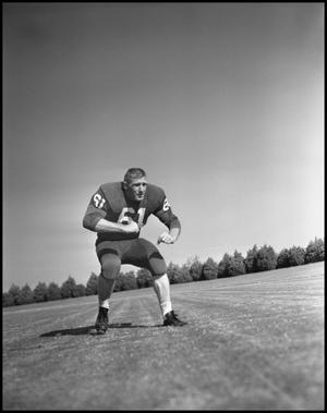 Primary view of object titled '[Football Player Number 61 in a Blocking Position, 1961-1962]'.
