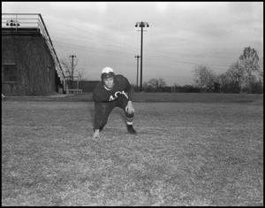 Primary view of object titled '[Football Player Kneels on the Field]'.