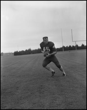 Primary view of object titled '[Football Player No. 45 Running with a Football, September 1962]'.