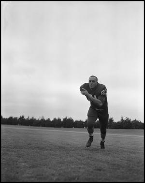 Primary view of object titled '[Football Player No. 61 Running on the Field, September 1962]'.