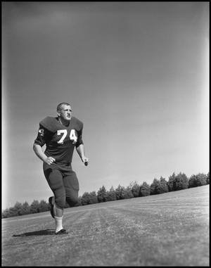 Primary view of object titled '[Jersey Number 74 Football Player in a Running Position, 1961-1962]'.