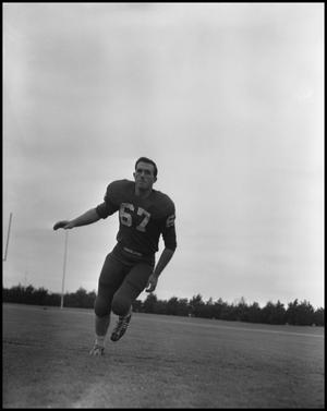 Primary view of object titled '[Football Player No. 67 Running on the Field, September 1962]'.