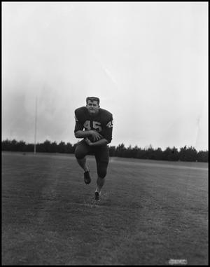 Primary view of object titled '[Football Player No. 45 Clutching the Ball to Himself, September 1962]'.