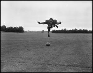 Primary view of object titled '[Football Player No. 64 in Midair, September 1962]'.