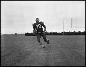 Primary view of object titled '[Football Player No. 32 Running with a Football, September 1962]'.